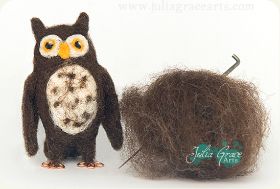 A needle felted owl sculpture next to the raw fleece and needle used