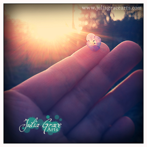 A delicate tiny flower on a fingertip, kissed by sun beams