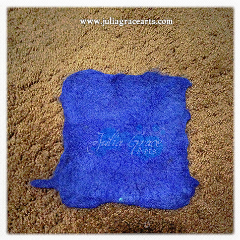 A square of wet felted blue wool